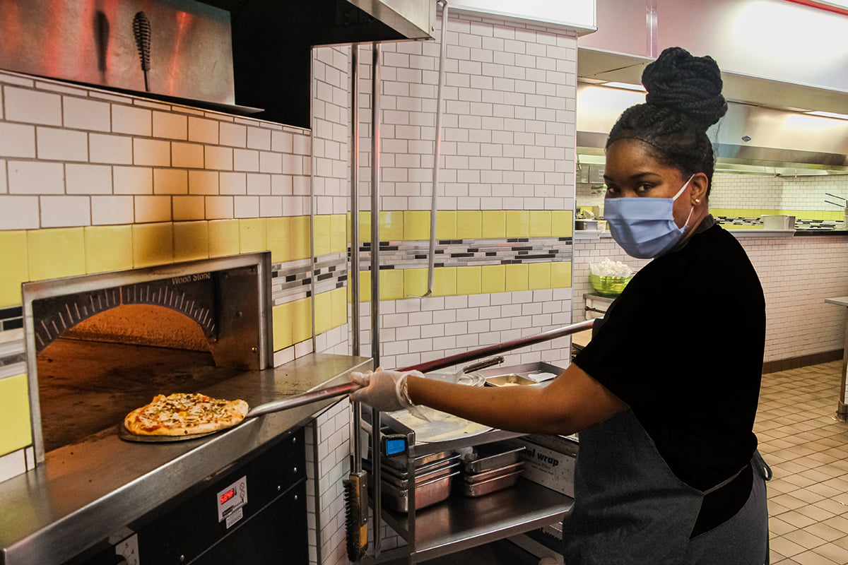 Dining team member takes a pizza out of the oven.