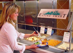 A person is serving themselves food from the dining commons.